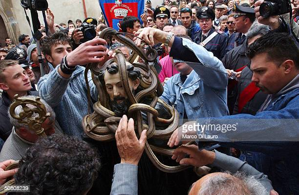 Snake charmers take back their snakes from the statue of St Dominic at the end of the traditional snake procession in the village of Abruzzo May 6...