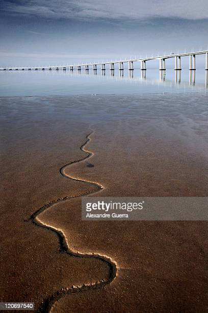 Snake like stream flowing to river with bridge