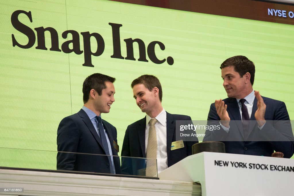 Snapchat co-founders Bobby Murphy, chief technology officer of Snap Inc., and Evan Spiegel, chief executive officer of Snap Inc., smile at each other after ringing the opening bell as Thomas Farley, president of the NYSE, looks on, March 2, 2017 in New York City. Snap Inc. priced its initial public offering at $17 a share on Wednesday and Snap shares will start trading on the New York Stock Exchange (NYSE) on Thursday.