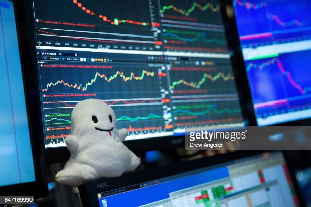 Snapchat logo stuffed animal sits on the desk of a trader on the floor of the New York Stock Exchange March 2 2017 in New York City Snap Inc shares...