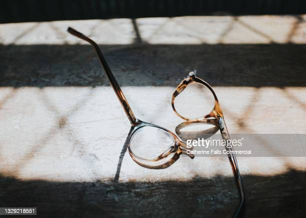 snapped spectacles on a sunny wooden table - temporary stock pictures, royalty-free photos & images
