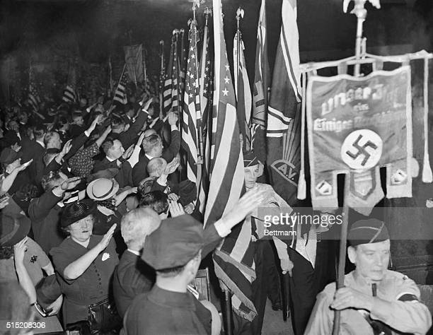 Snapping into the regulation Nazi salute Bund members hail the swastika banner as it is paraded in Madison Square Garden during opening ceremonies of...