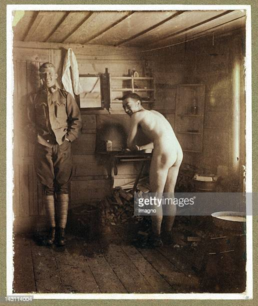Snapshot First World War Two austrian soldiers in a wooden house one of them dressed in uniform the other one nacked washing himself Photograph...