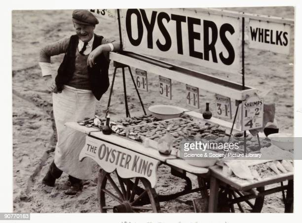 A snapshot photograph of a beach stall attendant taken about 1930 by an unknown photographer A man stands at a stall selling oysters whelks shrimps...
