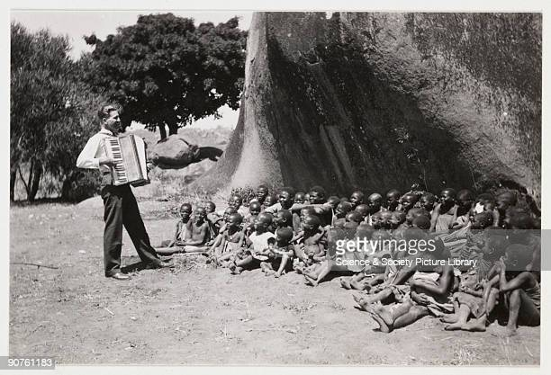 A snapshot photograph of a European man playing an accordion to a group of African children taken by an unknown photographer in about 1925 A large...