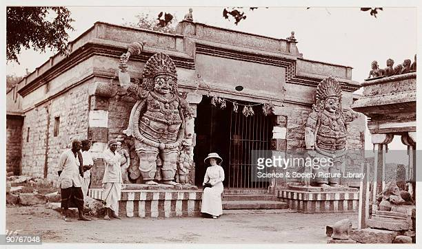 A snapshot photograph of a European woman sitting by one of the large statues flanking the entrance to the temple She wears a large hat to protect...