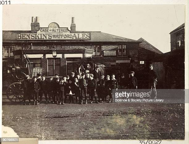 A snapshot photograph of a group of children outside a pub called �The Case is Altered� selling Benskin's Watford Ales The landlord was James...
