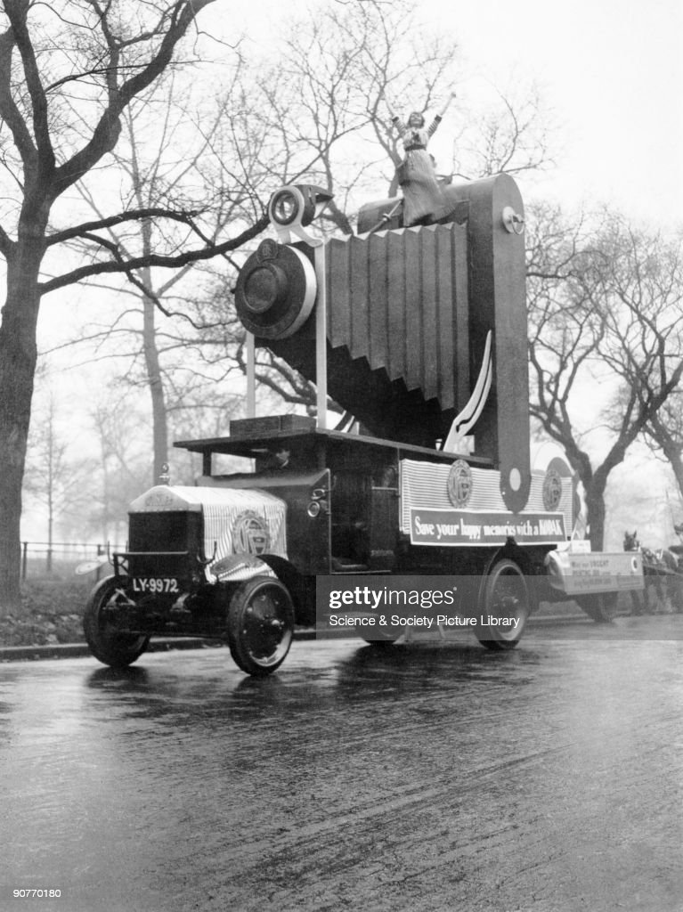 A snapshot photograph of a Kodak advertising float, taken by an unknown photographer in 1912. Probably made for a carnival parade, this float has a 'Kodak Girl' standing rather precariously on top of a giant folding camera carried on the back of a lorry. A poster on the side of the lorry reads - 'Save your happy memories with a Kodak'. The Kodak Girl in her distinctive striped dress was first used by Kodak Limited for advertising its products in 1910.