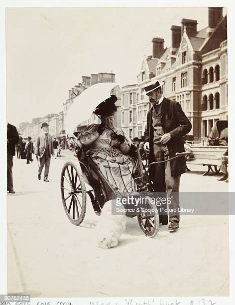 A snapshot photograph of a man and woman on a seafront parade taken by an unknown photographer in about 1900 A richly dressed woman sits in a...