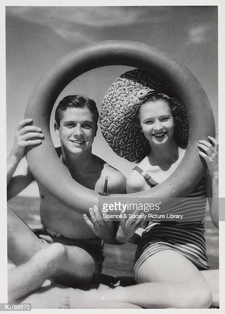 Snapshot photograph of a man and woman on the beach taken by an unknown photographer A smiling young couple in swimwear sit on the sand their faces...