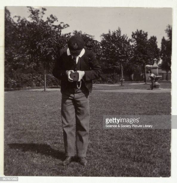 A snapshot photograph of a schoolboy taking a photograph taken by an unknown photographer in about 1905 The uniform suggests that he attends a smart...