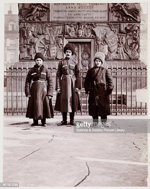 A snapshot photograph of a tourist posing with two Cossacks taken by an unknown photographer in about 1910 The tourist on the right is posing with...