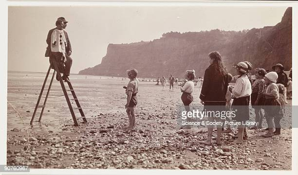A snapshot photograph of a ventriloquist with his dummy entertaining a small crowd of children on the beach Holidaymakers from the cities thrived on...