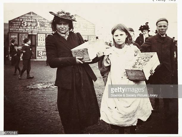 A snapshot photograph of a woman and girl in a market scene taken by an unknown photographer in about 1900 A woman and girl sell wares in a street...