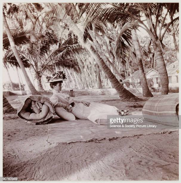 A snapshot photograph of a woman lying on the ground in the shade of a group of palm trees taken by an unknown photographer in about 1911 Wearing...