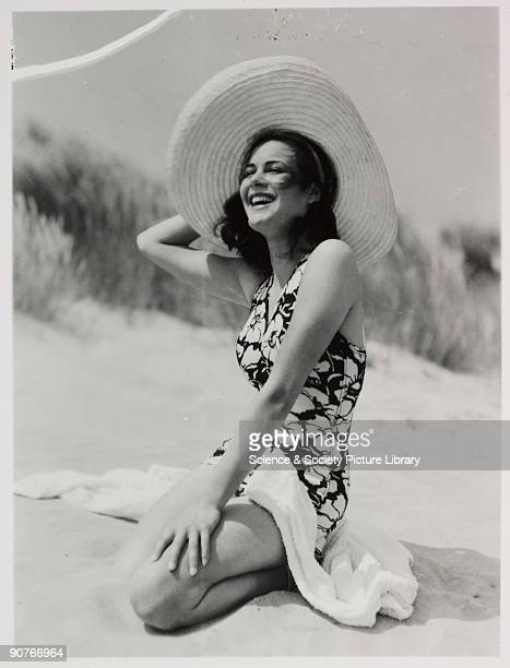 Snapshot photograph of a woman on a beach in Britain taken by an unknown photographer The woman wears a bold floral print swimsuit and holds on to a...