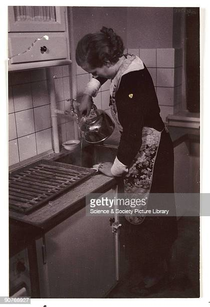 A snapshot photograph of a woman pouring water from a kettle into a kitchen sink taken by an unknown photographer in about 1935 Originally a shooting...