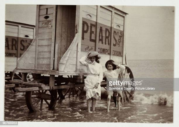 A snapshot photograph of a young woman and a girl at the seaside taken by an unknown photographer in about 1900 They hold onto their hats in the sea...