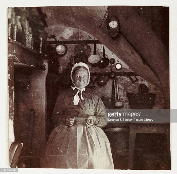 A snapshot photograph of an elderly woman in a kitchen taken by an unknown photographer in about 1900 Originally a shooting term the word 'snapshot'...