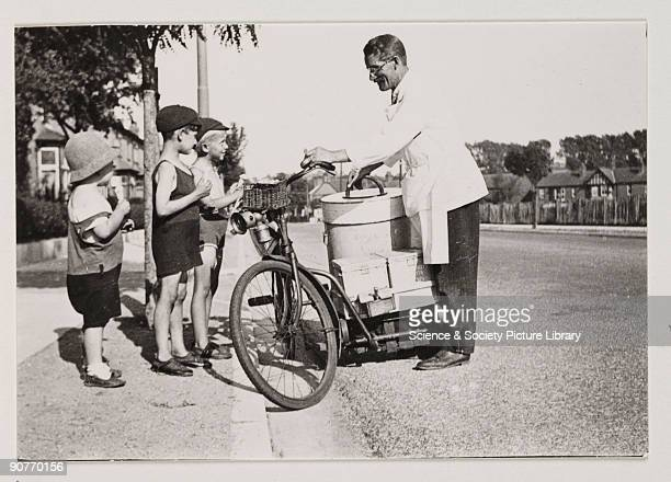 A snapshot photograph of an ice cream seller and three children taken by an unknown photographer in about 1925 Originally a shooting term the word...