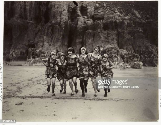 A snapshot photograph of six women running along a beach taken by an unknown photographer in about 1925 Six women link arms to run in line along the...