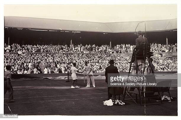 Snapshot photograph of two tennis players at Wimbledon, taken by an unknown photographer in 1936. Fred Perry is photographed here winning the Davis...