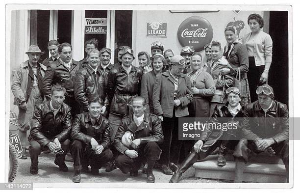 Snapshots. Group portrait of some motor-cycle drivers in front of a store. On the facade of the store some advertisement can be seen. Germany....