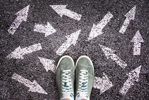 Sneaker shoes and arrows pointing in different directions on asphalt ground, choice concept 1136179001