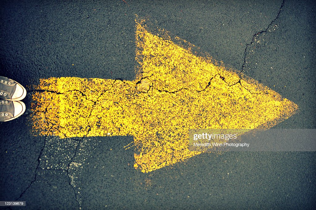 Sneakers and yellow arrow painted on asphalt : Stock Photo