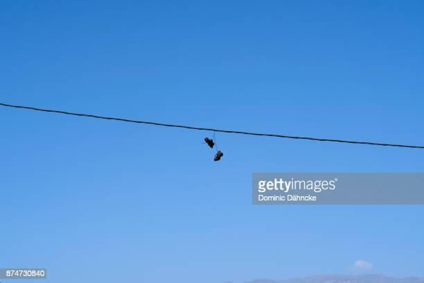 sneakers hanging from a cable - dähncke fotografías e imágenes de stock