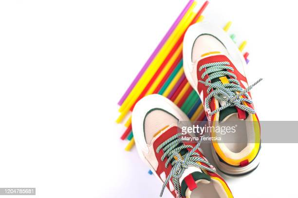 sneakers on a stack of tubes on an isolated white background. - multi colored shoe stock pictures, royalty-free photos & images