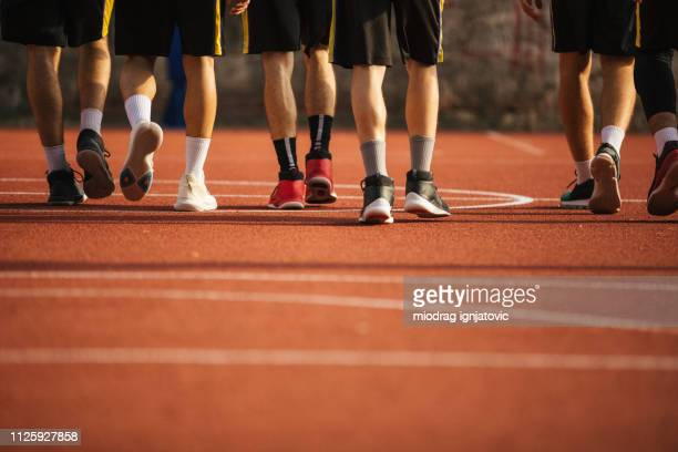 sneakers on basketball court - basketball shoe stock photos and pictures