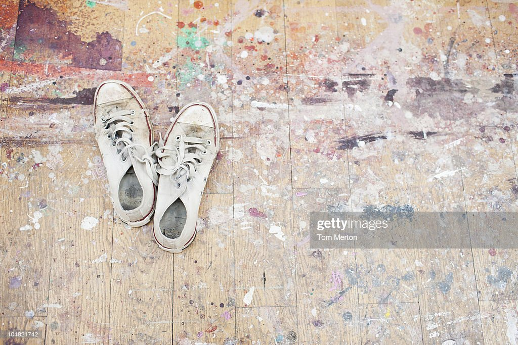 Sneakers on paint-spattered wood floor : Stock Photo