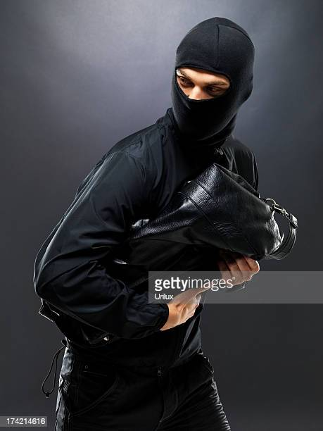 sneaky thief making off with some loot - thief stock pictures, royalty-free photos & images