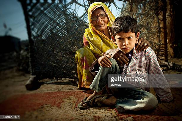 sneering little indian boy sitting on ground with his grandmothe - asian boy stock pictures, royalty-free photos & images