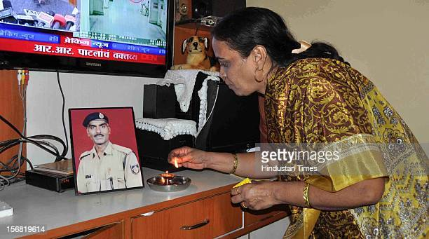 Snehalata wife of 26/11 Martyr Head Constable Murlidhar Choudhary lights the lamp in front of his picture to celebrate the news of Ajmal Kasab's...