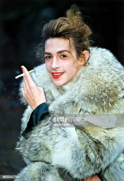 Sänger Chanson D Porträt mit einer Zigarette in der Hand geschminkt und mit einem Pelzmantel bekleidet
