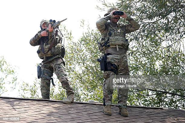 A sniper and a lookout stand on top of a roof searching for two men following the killing of a police officer Tuesday Sept 1 2015 in Fox Lake Ill
