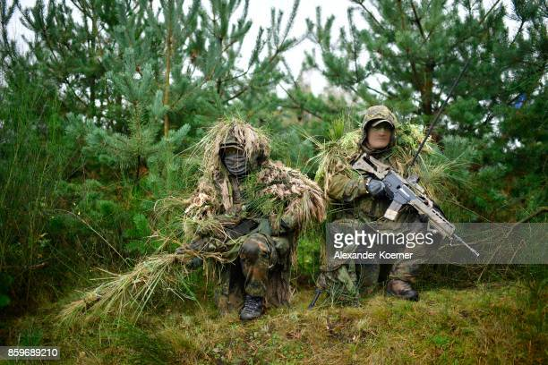 A sniper and his spotter soldiers of the Bundeswehr the German armed forces take part in a simulated attack during military exercises on October 10...
