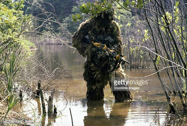 A sniper dressed in a ghillie suit crosses a stream while on patrol.