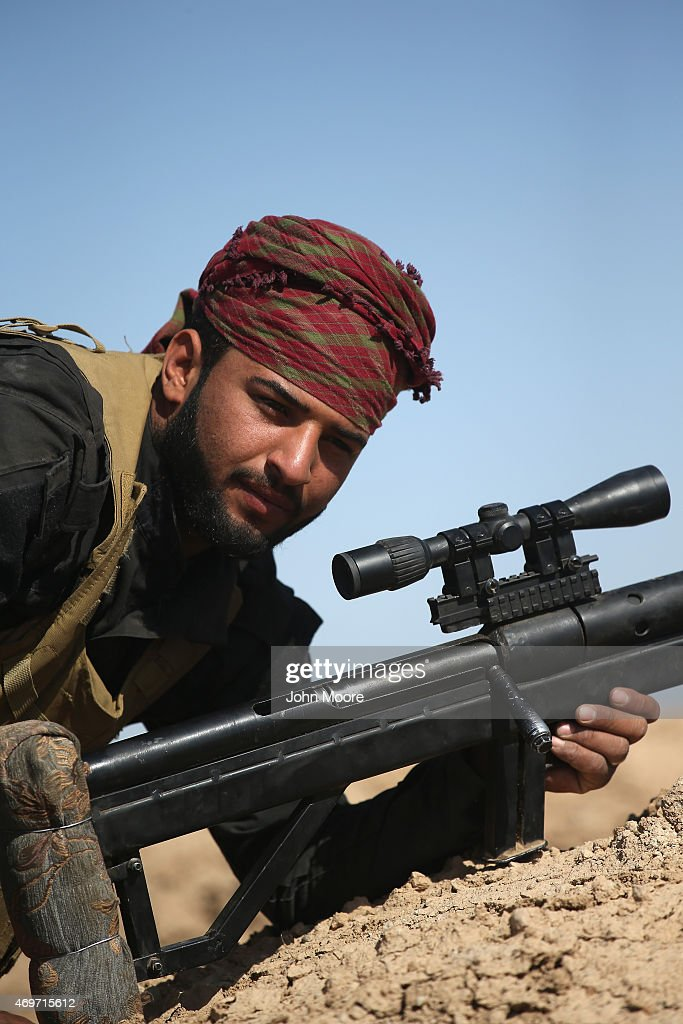 A sniper from the Abu al Fadhel al Abbas militia takes a frontline position in support of Iraqi Army troops as they assault ISIL fighters on April 14, 2015 near Al-Karmah, in Anbar Province, Iraq. The Iraqi government is trying to push ISIL back from frontline positions in the predominantly Sunni area which the extremists captured last year.