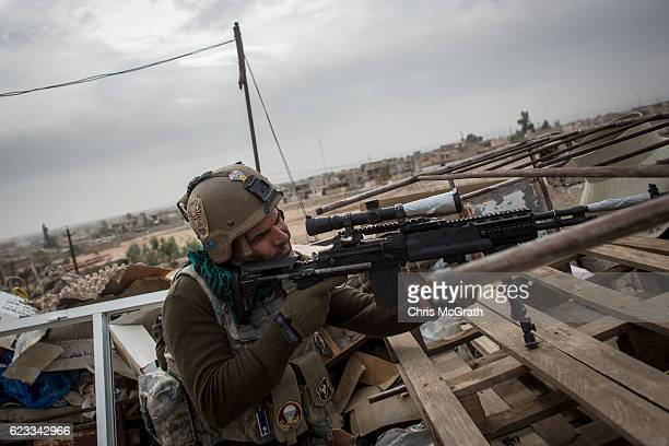 A sniper from the Iraqi Army Armoured Ninth Division looks for ISIL snipers across the frontline from a rooftop in the Entisar neighborhood on...