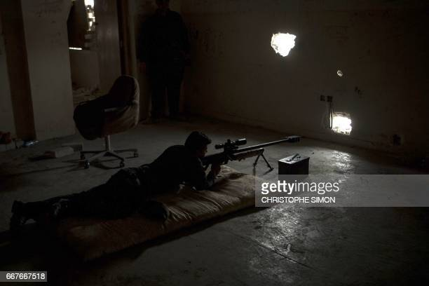 A sniper from the Iraqi federal police unit aims towards an Islamic State group position in west of Mosul on April 12 2017 during an ongoing...