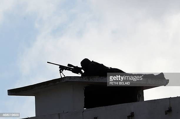 A sniper lies on top of a building as Tunisian special forces keep watch during a march against extremism outside Tunis' Bardo Museum on March 29...
