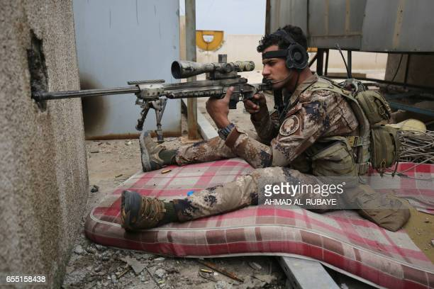 TOPSHOT A sniper member of the Iraqi forces consisting of the Iraqi federal police and the elite Rapid Response Division takes aim during their...