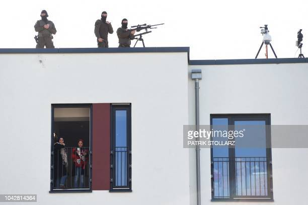 A sniper of the police is seen on September 29 2018 on the roof of a building as two women stand at a window prior to the visit of the Turkish...