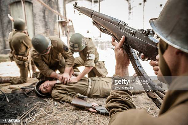 WWII Sniper Providing Cover for Medic Working on Wounded Soldier