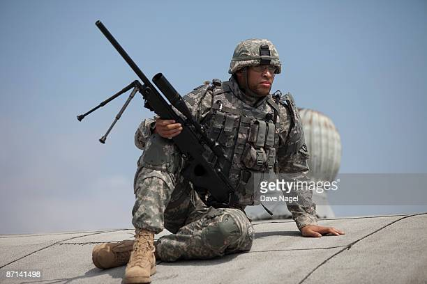 sniper sitting on a rooftop in an urban setting - us army urban warfare stock photos and pictures