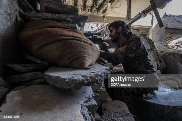 YPG sniper takes high position in a high building overlooking ISIS position close to the national hospital of Raqqa He says that ISIS uses civilians...