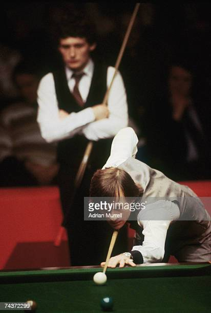 Snooker player Alex Higgins takes a shot during a match against Jimmy White who is in the background 1980s